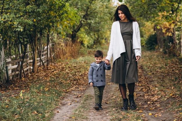 Mãe com filho pequeno em um parque de outono Foto gratuita