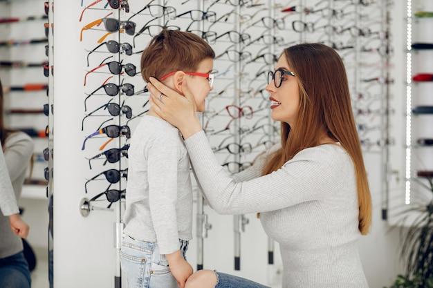 Mãe com filho pequeno na loja de óculos Foto gratuita