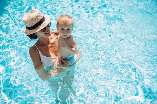 Mãe com filho se divertindo na piscina Foto gratuita