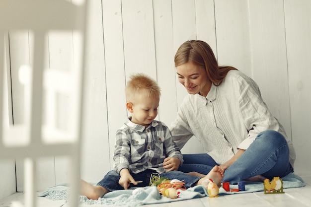 Mãe com filho se preparando para a páscoa em casa Foto gratuita