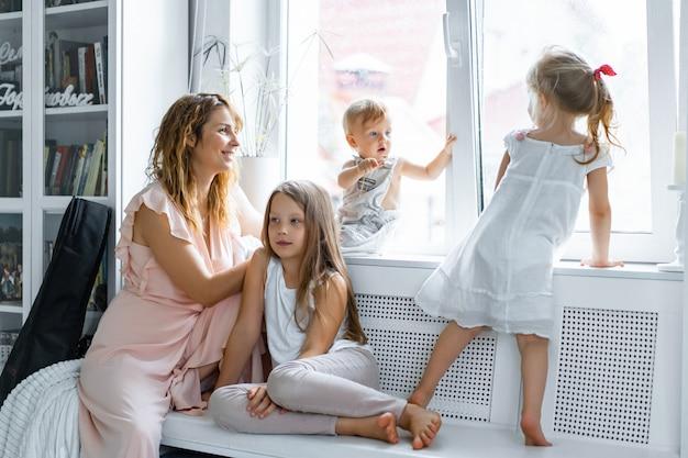 Mãe com filhos em um ambiente caseiro. crianças pela janela Foto gratuita