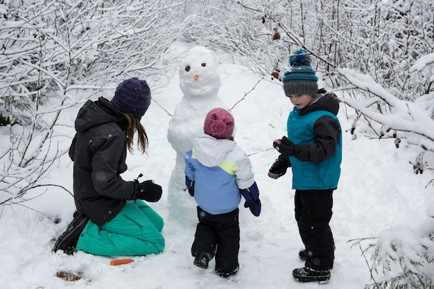 Mãe com filhos fazendo boneco de neve Foto gratuita
