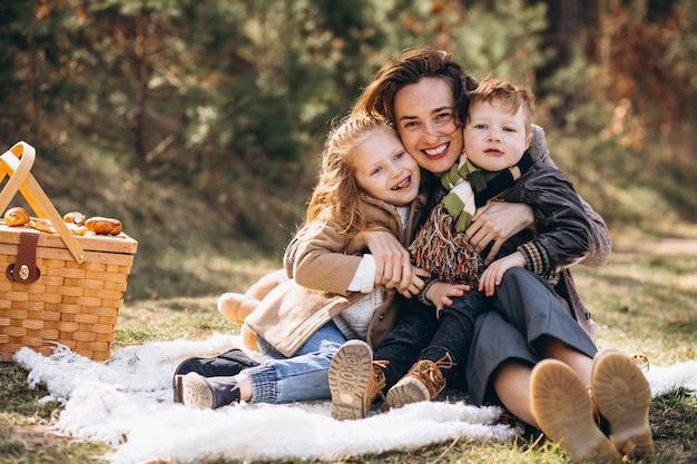 Mãe com filhos fazendo piquenique na floresta Foto gratuita
