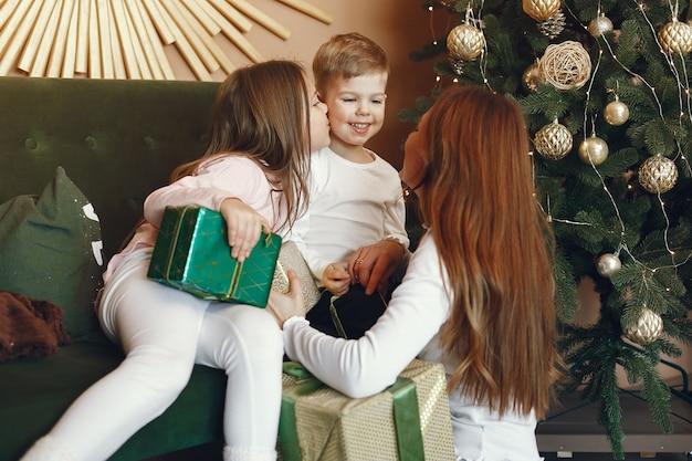 Mãe com filhos fofos perto da árvore de natal Foto gratuita