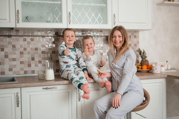 Mãe com filhos tomando café na cozinha Foto Premium