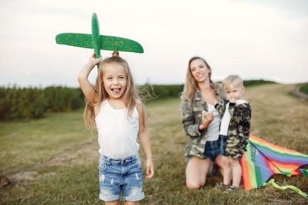 Mãe com giros filhinhos em um campo de verão Foto gratuita