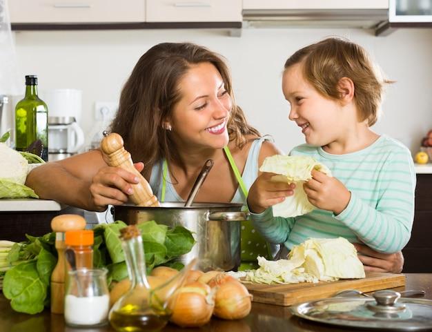 Mãe com pequena filha cozinhando em casa Foto gratuita