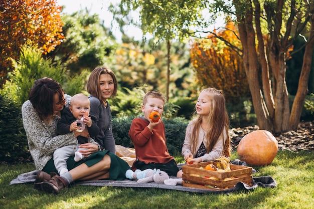 Mãe com quatro filhos fazendo piquenique no quintal Foto gratuita