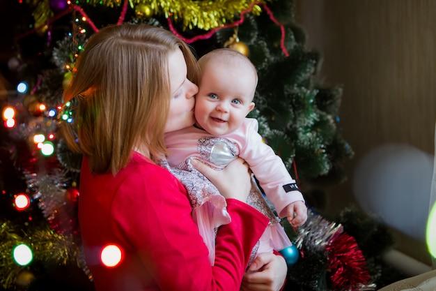Mãe com seu bebê com uma árvore de natal Foto Premium