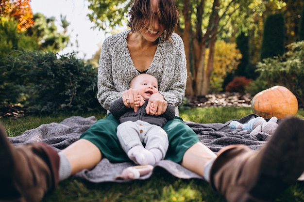 Mãe com seu filho pequeno fazendo piquenique em um quintal Foto gratuita