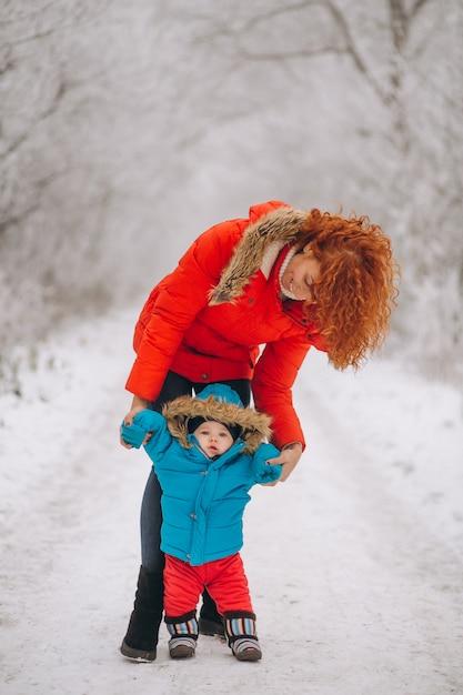 Mãe com seu filho pequeno juntos em um parque de inverno Foto gratuita