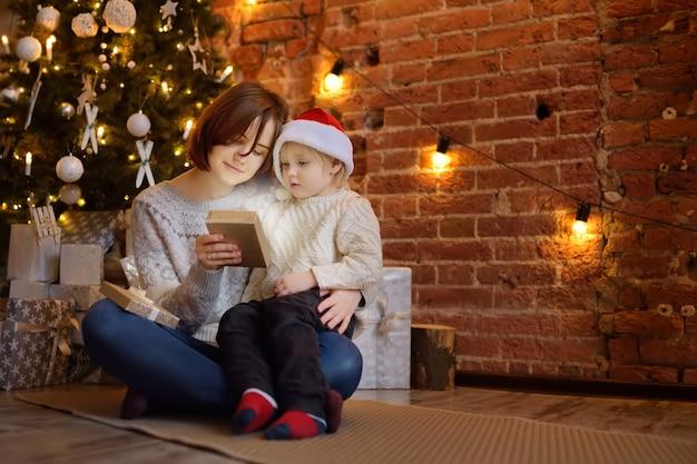 Mãe com seu filho pequeno, lendo um livro de magia na acolhedora sala de estar. tempo para a família nos feriados Foto Premium