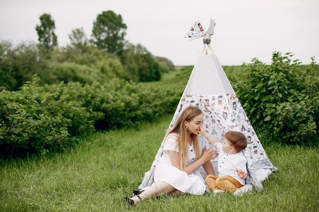 Mãe com sonplaying em um campo de verão Foto gratuita