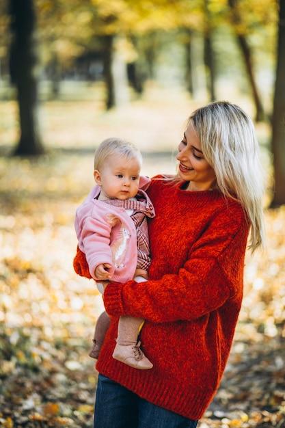 Mãe com sua filha bebê no parque no outono Foto gratuita