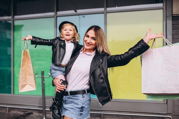 Mãe com sua filha bonita com sacolas de compras Foto gratuita