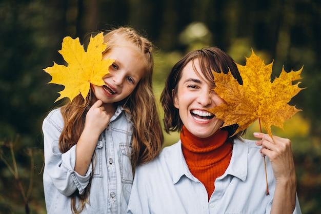 Mãe com sua filha na floresta cheia de folhas douradas Foto gratuita