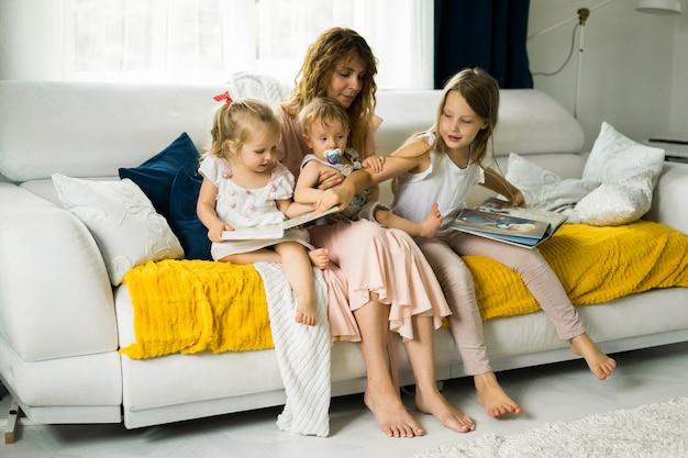 Mãe com três filhos, lendo um livro em uma atmosfera caseira Foto gratuita