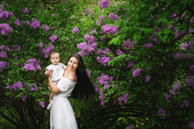 Mãe com um bebê em uma caminhada no jardim florido da primavera Foto Premium