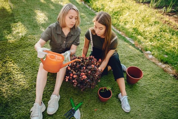 Mãe com uma filha trabalha em um jardim perto da casa Foto gratuita