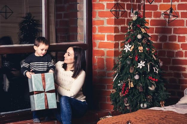 Mãe dá um presente para o filho no natal. Foto Premium
