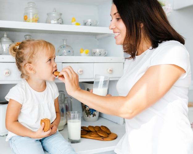 Mãe dando um biscoito para a filha Foto gratuita