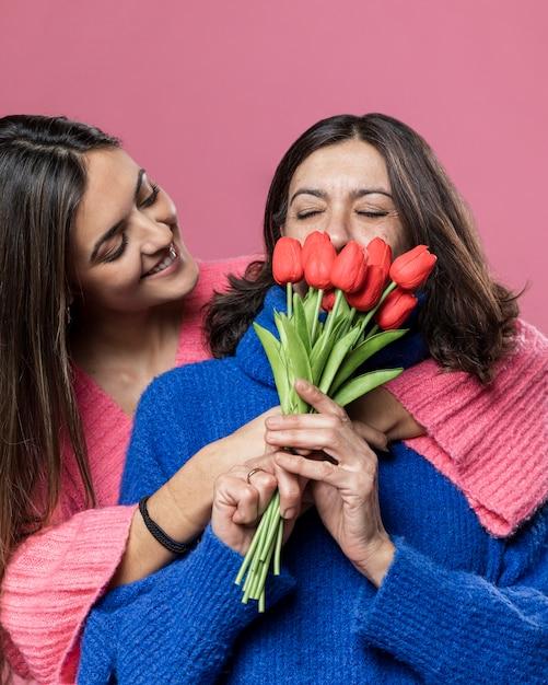 Mãe de baixo ângulo cheirando flores da filha Foto gratuita