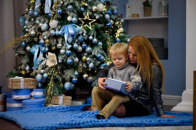 Mãe de família feliz e bebê pequeno filho brincando em casa nas férias de natal. feriados de ano novo Foto Premium
