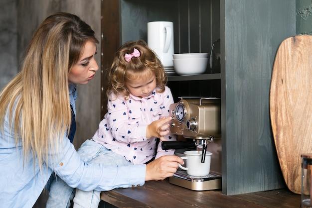 Mãe de vista lateral fazendo café com a filha Foto gratuita