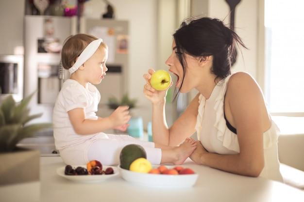 Mãe doce, alimentando seu bebê na cozinha Foto Premium