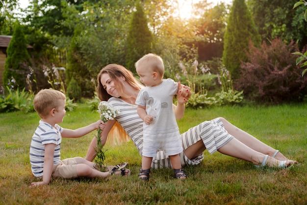 Mãe, dois filhos descansam na natureza. rivalidade entre irmãos. irmãos, maternidade. Foto Premium