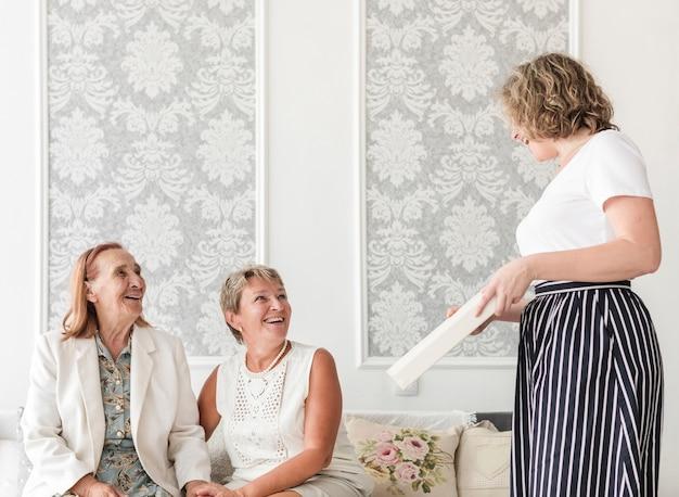 Mãe e avó olhando sua filha segurando o álbum de fotos em casa Foto gratuita
