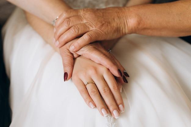 Mãe e avó segura a mão da noiva Foto gratuita