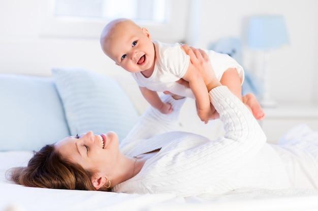 Mãe e bebê em uma cama branca Foto Premium