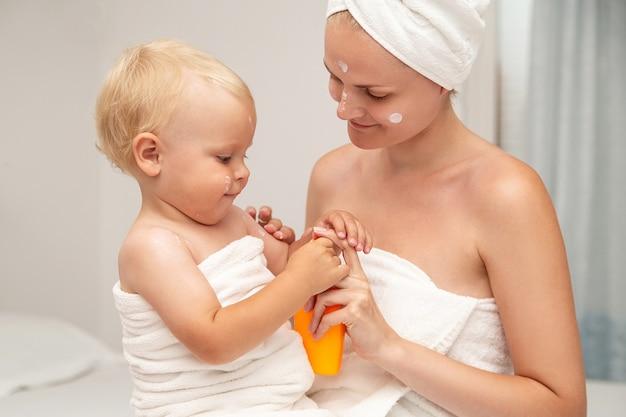 Mãe e bebê infantil em toalhas brancas aplicam protetor solar ou após loção ou creme de sol. Foto Premium