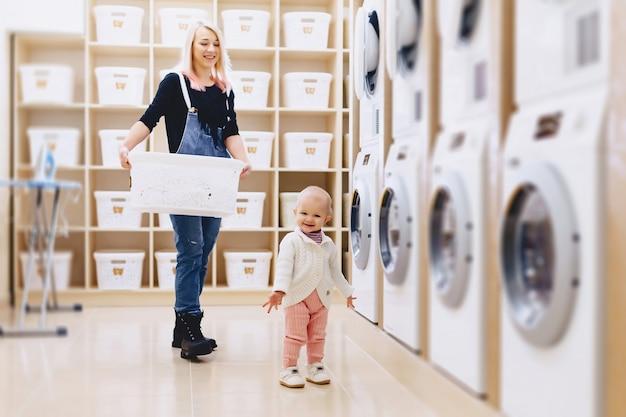 Mãe e bebê na lavanderia levar as coisas e brincar Foto Premium