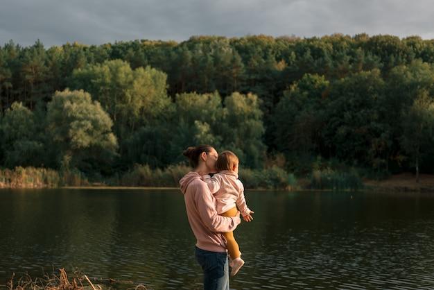 Mãe e bebê sentado perto do lago. viagem local. novas férias normais. dia das mães Foto Premium