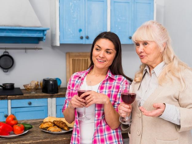 Mãe, e, dela, filha jovem, ficar, em, cozinha, segurando, copos de vinho, em, mãos Foto gratuita