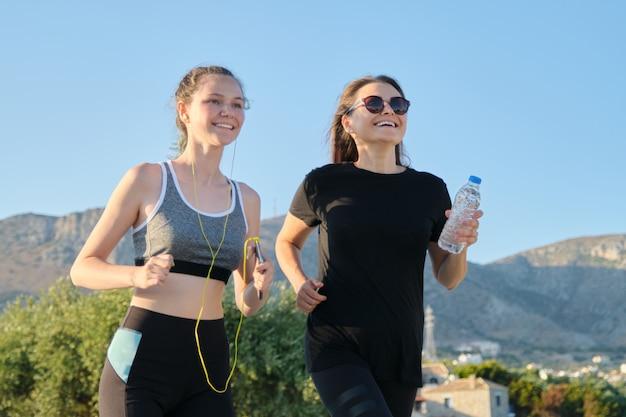 Mãe e filha adolescente correndo ao ar livre Foto Premium