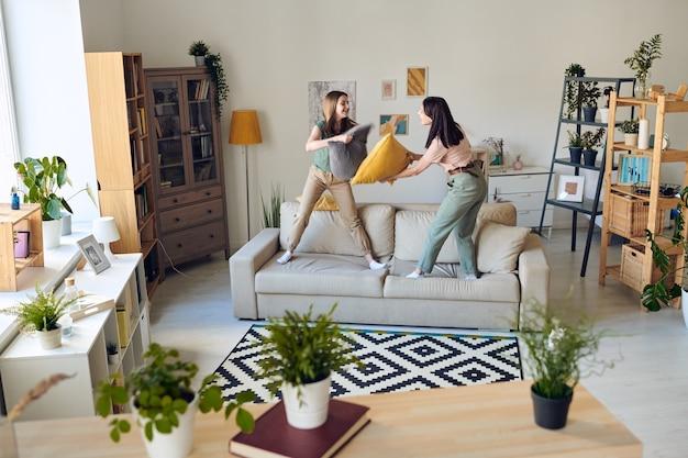 Mãe e filha adolescente em pé no sofá e lutando contra o travesseiro na sala de estar Foto Premium