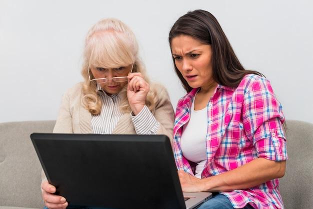 Mãe e filha adulta olhando para laptop com curiosidade Foto gratuita