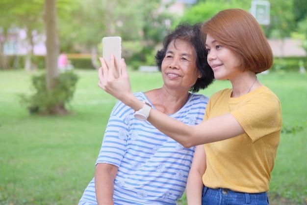 Mãe e filha asiática de meia-idade está tirando uma selfie com um smartphone com um sorriso e sendo feliz no parque é um calor impressionante Foto Premium