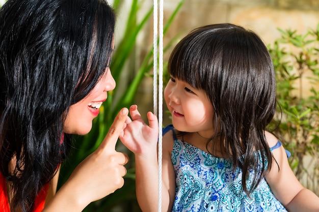 Mãe e filha asiáticas em casa no jardim Foto Premium