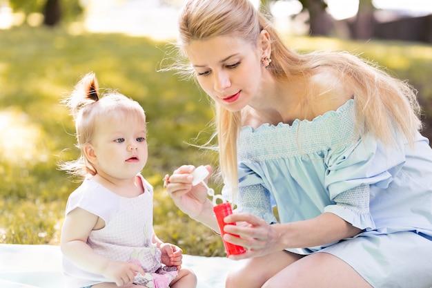 Mãe e filha bebê soprando bolhas de sabão ao ar livre Foto Premium