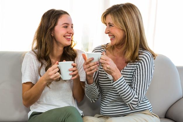 Mãe e filha bebem chá em casa Foto Premium
