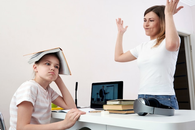 Mãe e filha brigando por lição de casa, mãe chateada está com raiva da filha entediada, educação em casa, mal-entendido Foto Premium