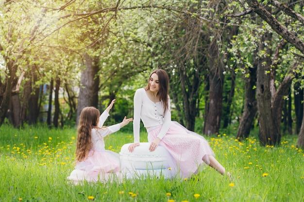 Mãe e filha caminham na primavera florescendo apple Foto Premium