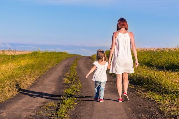 Mãe e filha caminham por uma estrada rural ao longo de um campo de trigo em  um dia quente de verão | Foto Premium