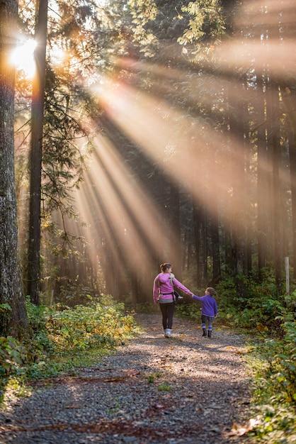 Mãe e filha caminhando em uma floresta com raios de sol Foto Premium