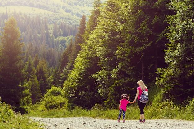 Mãe e filha caminhando pela estrada da montanha Foto Premium