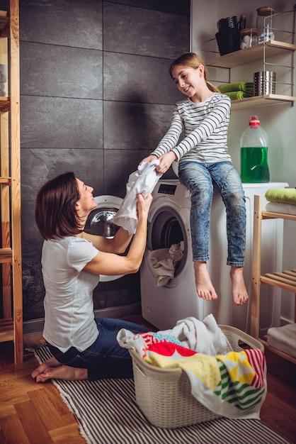 Mãe e filha colocando as roupas em uma máquina de lavar Foto Premium